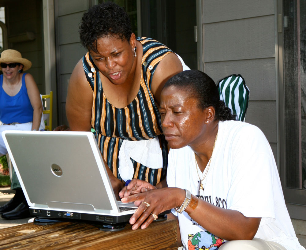 Exploring family history at the McNair Brazil Scott Family Reunion in Milwaukee, Wisconsin. Cousins Candace Wilcher (left, Brazil branch) and Shelley Mathews (McNair branch) take the opportunity of the reunion to review family genealogy.