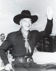 Hopalong Cassidy waving to admirers.