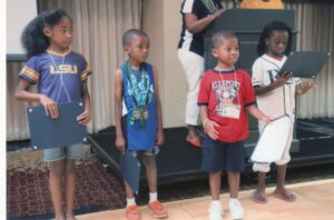 """During the banquet, at the Neal Family Reunion, certificates were presented to Young Family Achievers. Certificates for several age groups recognized individual accomplishments also chronicled in the family reunion booklet. Here """"Seedling Awards"""" are given to the youngest group (left to right) Lillian Nabors (6), Ethan Parrish (5), Amaris Johnson (5), and Karys Rhodan (7). Members wore favorite team shirts for the banquet."""