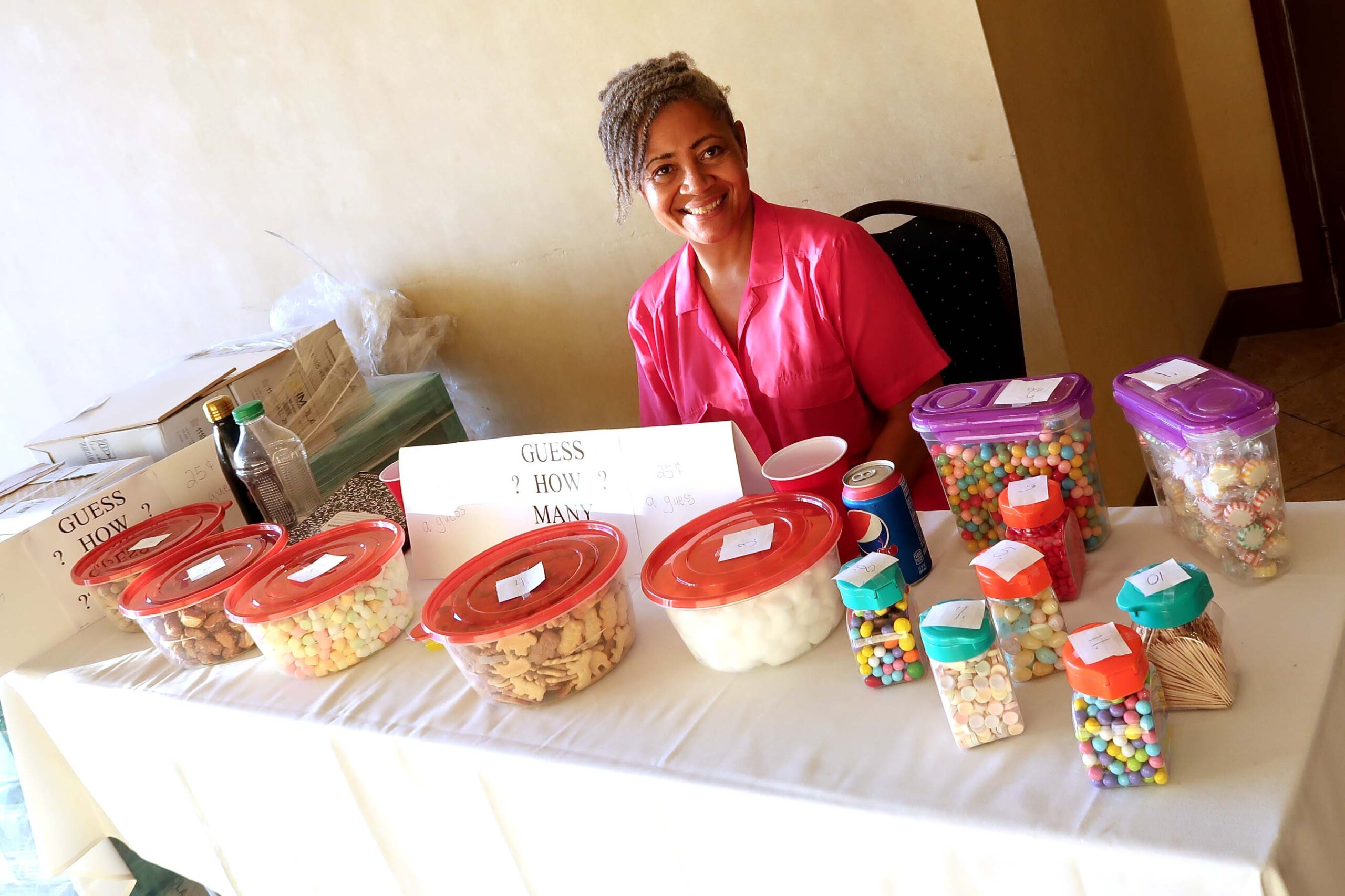 There was a guessing game table at the entrance to the Johnson-Barnes Family Reunion Meet and Greet. Liz Osborne overseeing containers of peanuts, M&Ms, toothpicks, cotton balls, and other items. Members wrote their guess(s) of numbers in each container and closest to correct numbers won. Winners were announced at the banquet and prizes were the containers