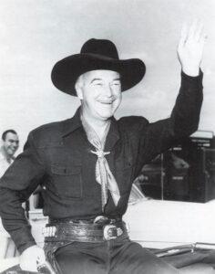Hopalong Cassidy waving to admirers.