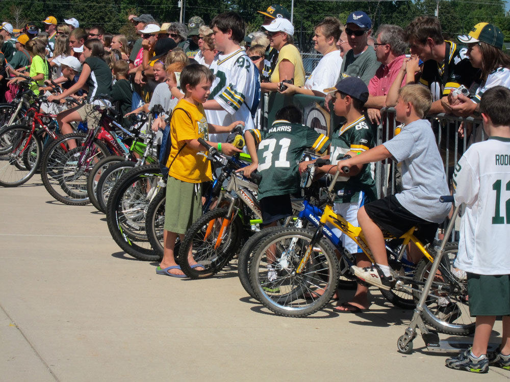 Kids line up hoping a Packer, coming from the locker room, will want to ride their bike or scooter to the practice field several blocks away.